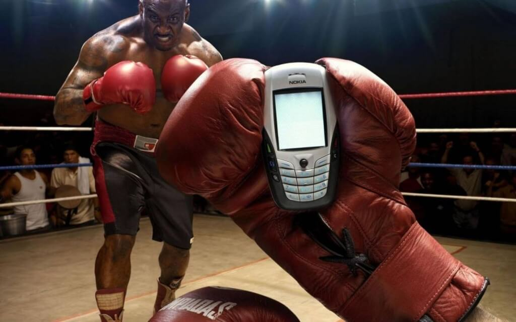 Boxer holding mobile phone in the ring