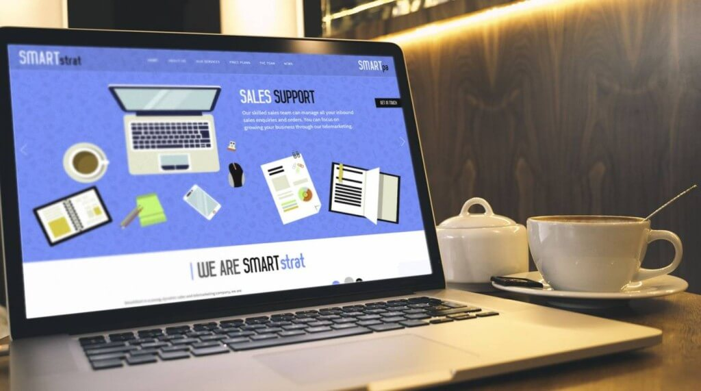 SMARTstrat new website on laptop next to coffee