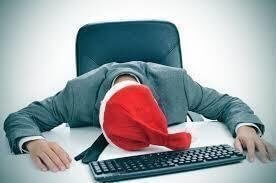Tired worker with santa hat resting on desk